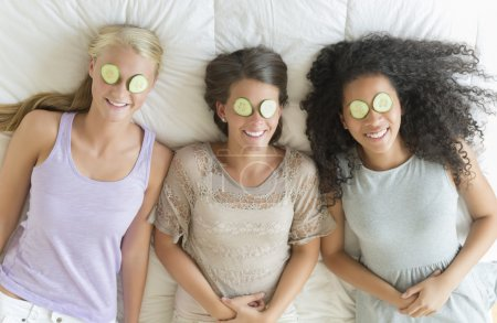 Happy Teenage Girls With Cucumber Slices On Their Eyes