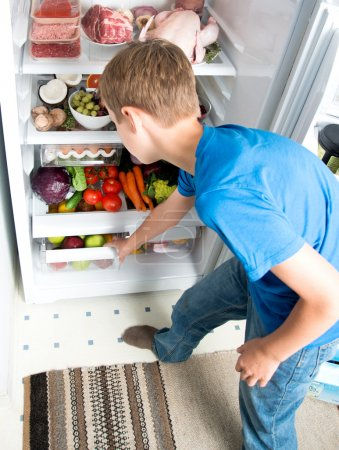 Young Boy Reaching for Snack in Refrigerator