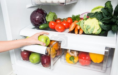 Hand Reaching for Snack in Refrigerator Full of Healthy Food Options