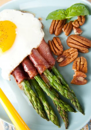 Healthy Paleo Breakfast with Asparagus Wrapped in Prosciutto, Fried Egg, and Raw Pecan Halves