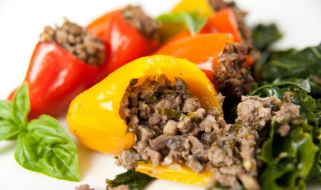 Foto de Carne de res y verduras rellenas mini pimientos servidos con col rizada marchita - Imagen libre de derechos