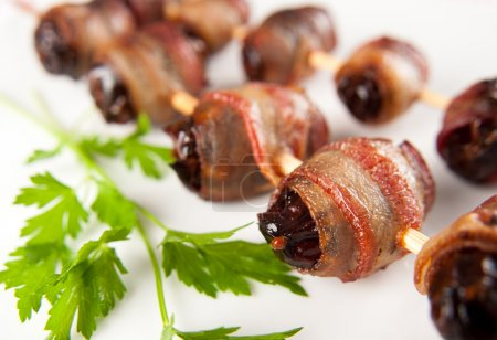 Photo for Medjool Dates Wrapped in Bacon and Baked on Skewers - Royalty Free Image