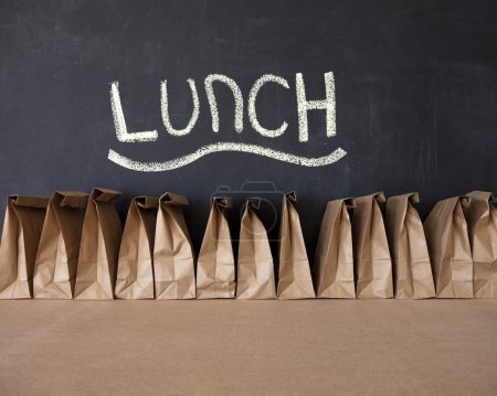 A row of brown bags against a blackboard....