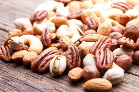 Photo for Nuts mix, with almond, cashews, pistachios, pecans, hazelnuts on wood plank background - Royalty Free Image