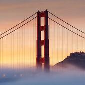 Golden Gate Bridge at sunset with fog