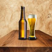 Bottle and glass of cold beer on wood table