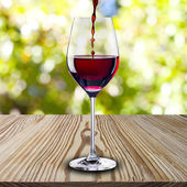 Red wine pure into glass on wood table