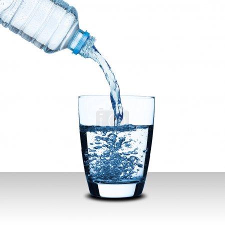 Wasser aus der Wasserflasche ins Glas gießen