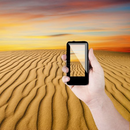 Cell phone in hand and desert view