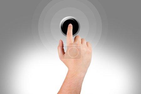 Man's hand pushing a black button