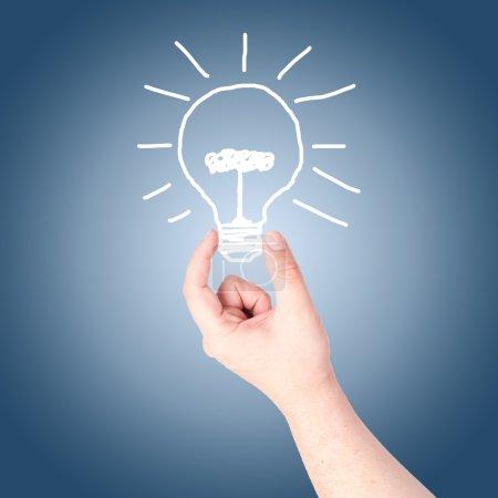 Hand holding on hand draw light bulb