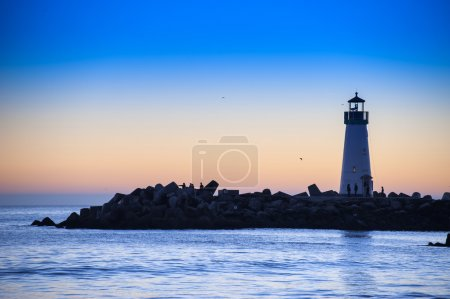 Photo for Lighthouse with light beam at sunset - Royalty Free Image