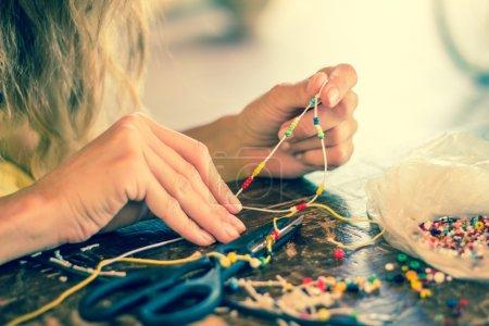 Photo pour Mains de femme faisant un bracelet avec une corde et des perles colorées, passe-temps . - image libre de droit