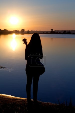 Silhouette of a lonely girl with a guitar by the river