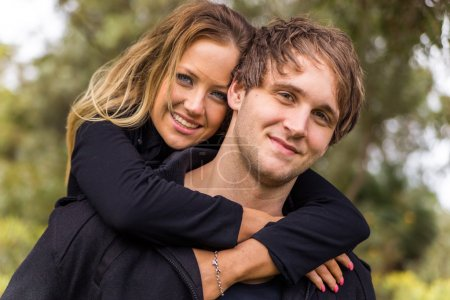 Happy young attractive couple portrait, smiling in outdoor environment