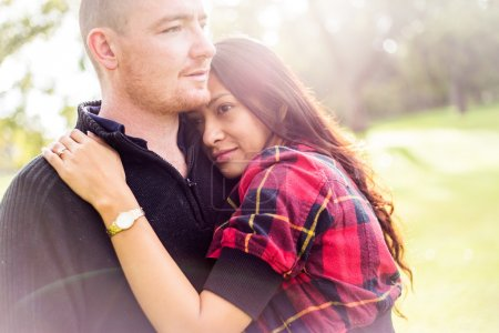 Romantic young couple portrait, asian woman, caucasian man, hugging tenderly in outdoor environment and beautiful light