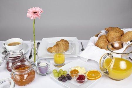 Photo pour Une table de petit déjeuner bien agencée avec une tasse de café, un panier de croissants et de petits pains, confiture de fraises et d'abricots et décoration d'un feu chauffe-plat et d'une gerbera de rose - image libre de droit