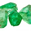 Four rich green emerald crystals on white...