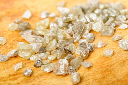 Photo for A pile of white grey uncut and rough diamonds on birch wood - Royalty Free Image