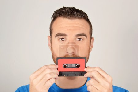 Man with tape cassette in the face