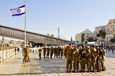 A squad of Israeli soldiers on the square near the Western Wall under national flag (Jerusalem)