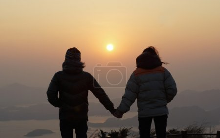 Boyfriend and girlfriend holding hand, hand in hand in the first day sunrise a new year on the peak landscape with beautiful skyline in good morning background