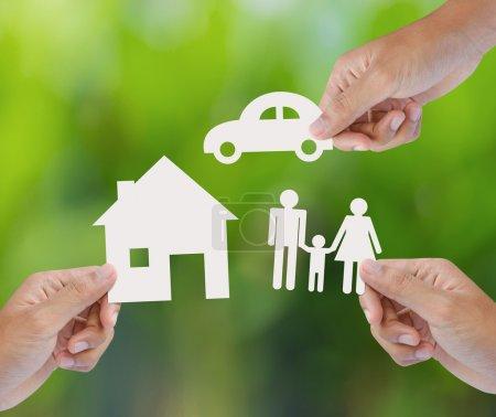Photo pour Main tenant un papier maison, la voiture, la famille sur fond vert, notion d'assurance - image libre de droit