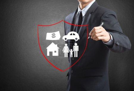 Photo pour Homme d'affaires dessin bouclier protégeant la famille, maison, voiture, argent. notion d'assurance - image libre de droit