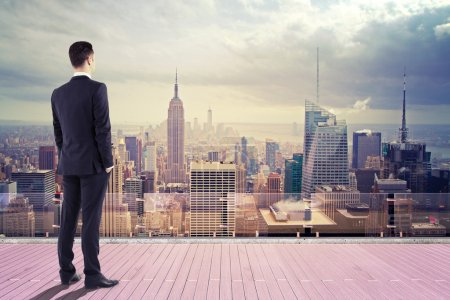 Photo for Businessman standing on roof and looking at city - Royalty Free Image