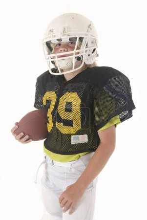 Young boy in American football uniform folding arms