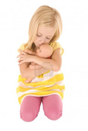 Cute young blond girl playing with a baby doll