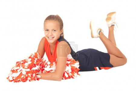 Young high school cheerleader laying down with pom poms