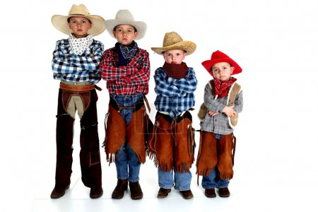 Young cowboy brothers standing arms folded serious...