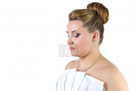 Woman in white wedding dress looking down