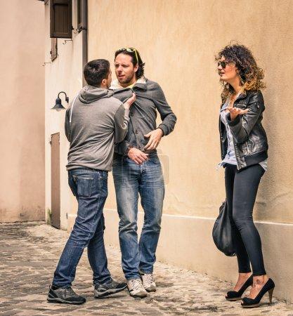 Photo pour Action en direct d'un gars sur l'agression à un autre gars pour obtenir le contrôle de la fille . - image libre de droit