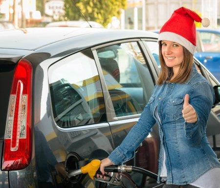 Photo pour Jeune femme à la station service avec chapeau de Père Noël - image libre de droit