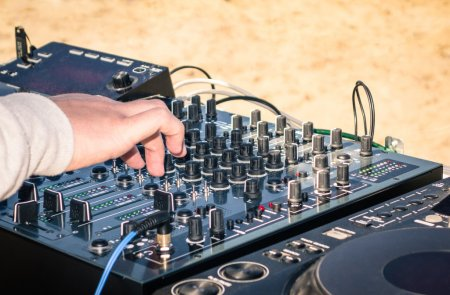 Hand of a deejay playing music on professional mixing controller