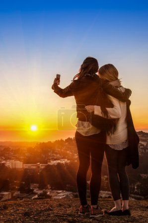 Couple of young women best friends taking a selfie during sunset