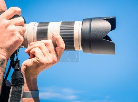 Photo pour Photographe en plein air avec gros zoom numérique lentille comme matériel professionnel s'apprête à tirer sur une photo - image libre de droit