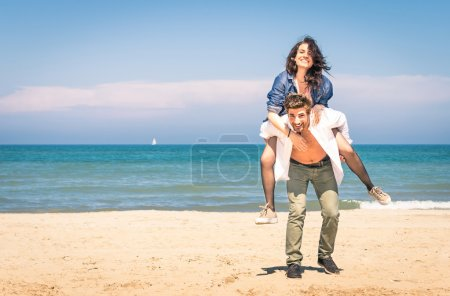 Young couple playing at the beach having fun with a piggyback jump - Happy man and woman at the beginning of a love story