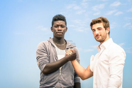 Afroamerican and caucasian men shaking hands in a modern handshake to show each other friendship and respect - Arm wrestling against racism