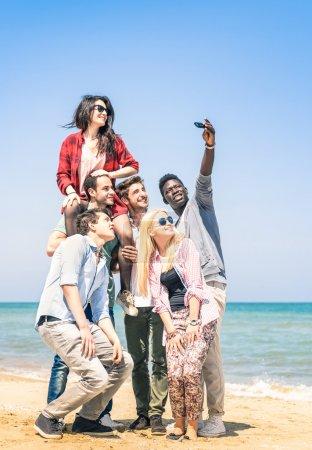 Foto de Grupo de amigos felices multirraciales tomando un selfie en la playa - concepto de amistad internacional todos junto contra el racismo - Imagen libre de derechos