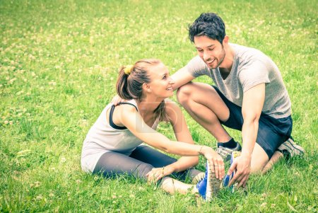 Happy couple training in the park - Young man and woman during summer workout and sport activity - Male and female fitness models stretching leg muscles after running - Vintage filtered look