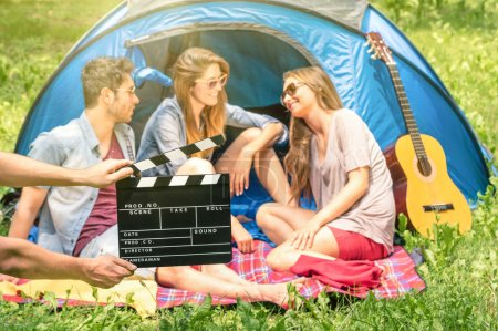 Group of friends camping in the park - Ciak clapperboard with young actors in the nature - Concept of youth and frienship with vintage scenario