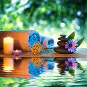 Dvě svíčky a ručníky černé kameny a fialové daisy na vodě