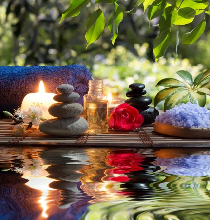Massage in the garden: candles, towels, stones and almond flowers in water