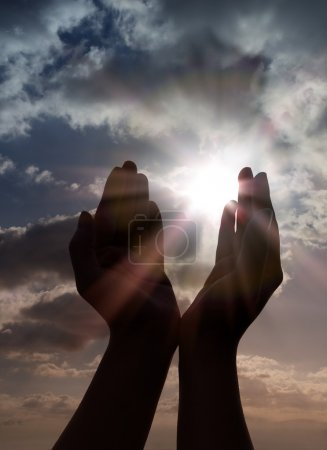 Prayer with hands to sun