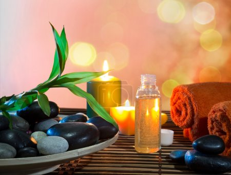 Preparation for massage in orange with dish, oil and bamboo
