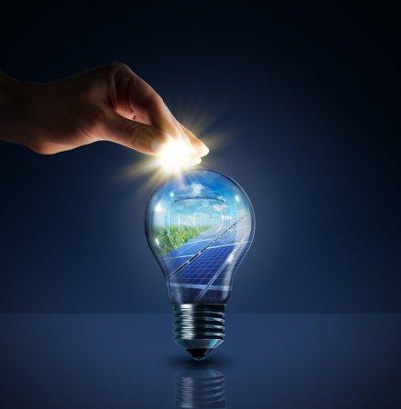 Foto de Invertir en energía solar - concepto - sol en la bombilla - alcancía - Imagen libre de derechos