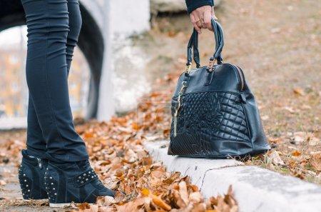 The female hand takes a black ladies' handbag....